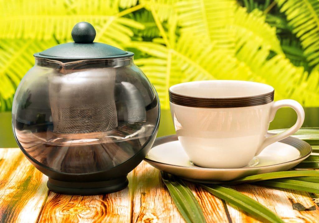 Chá de cardo-mariano servido em uma xícara e um pires de porcelana branco com uma faixa verde. Ao lado um bule de chá. As peças estão sobre uma mesa de madeira decorada com uma folhagem.