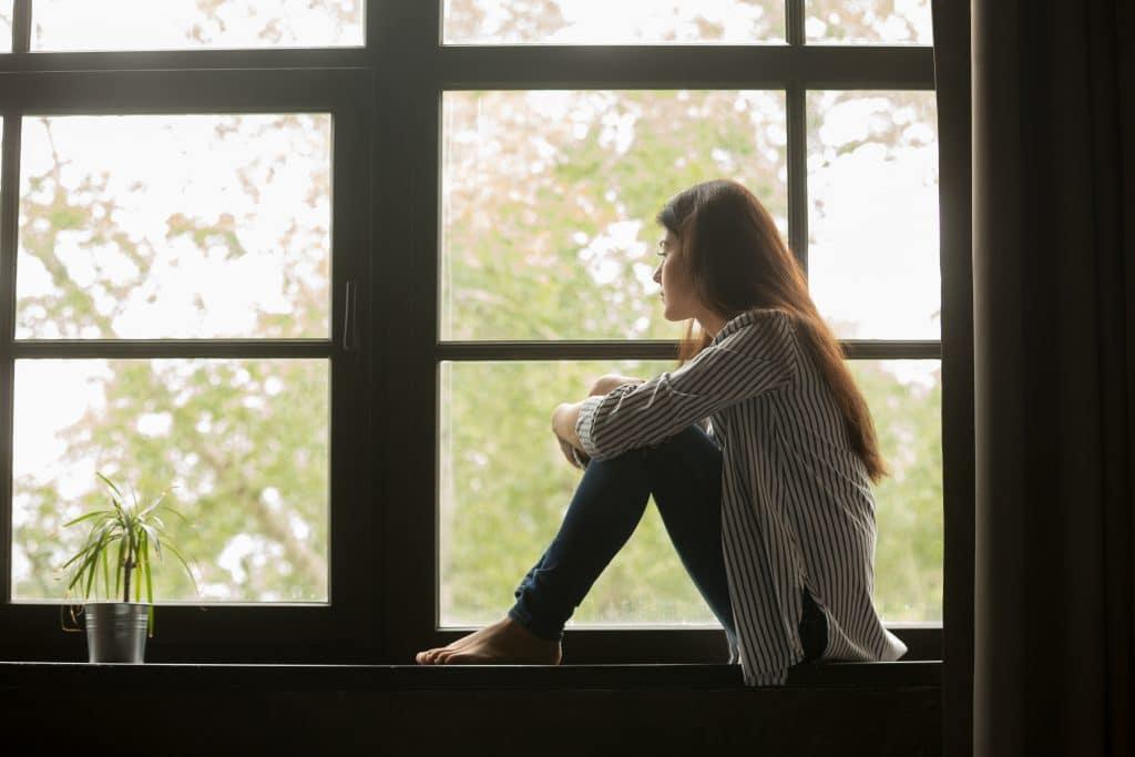 Jovem mulher de cabelos longos sentada de frente para uma grande janela de vidro. Ela está olhando para o infinito. Ao lado, um vaso com uma planta compõe o cenário.