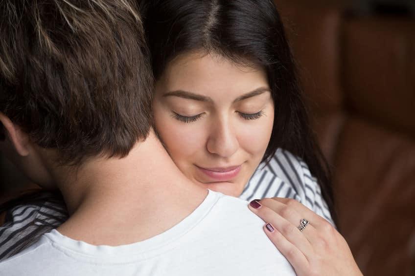 Mulher de olhos fechados sorri enquanto abraça homem, em sinal de agradecimento.
