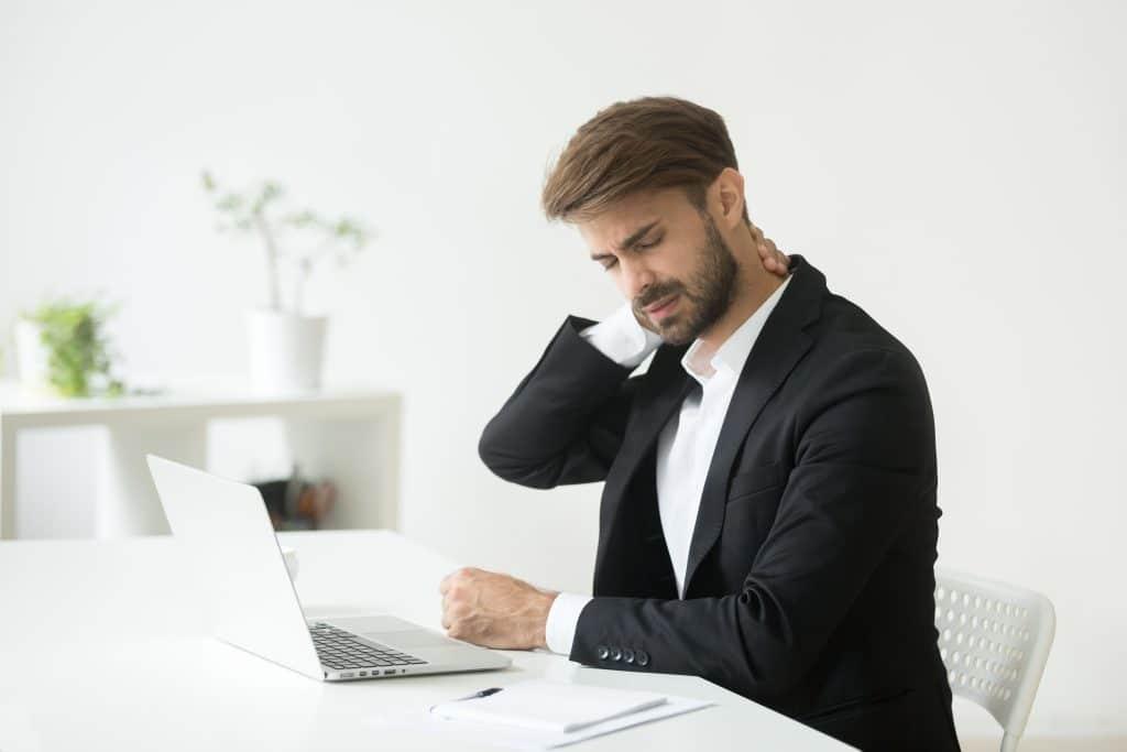 Homem de terno em uma sala do seu escritório Ele está de frente para o notebook. Aparentemente está com dores na nuca, pois uma de suas mãos está sobre ela.