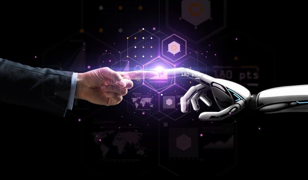 Mão de um robô e mão humana se tovcando sobre uma projeção virtual.