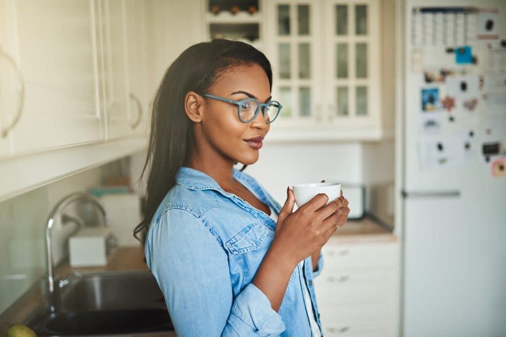 Mulher afrodescendente em sua cozinha. Ela está pensativa, segurando uma xícara de café brnaca. Ela usa óculos e uma linda camisa jeans azul clara.
