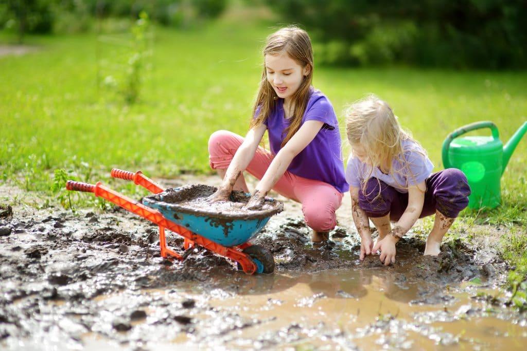 Duas crianças brincando na lama. Elas estão em um jardim. Uma delas está colocando as mãos em uma carriola cheia de lama e a outra mexendo na lama que está no chão.