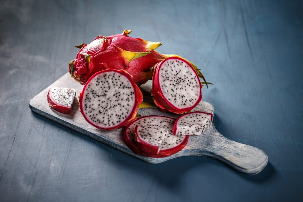 Várias pitayas sobre uma tábua de cortar carnes. Uma das frutas está inteira e a outra cortada ao meio e também fatiada.