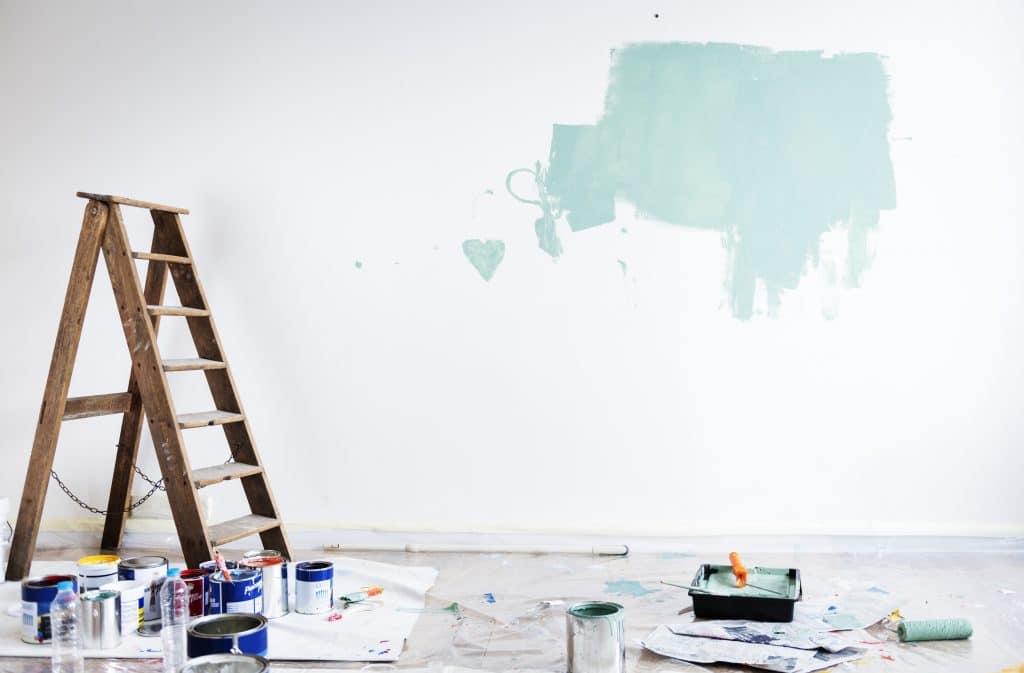 Escada de madeira. Ela está sendo utilizada para alguma pessoa pintar a parede branca. Ao redor da escada vários baldes de tinta. Ao chão uma vasilha com tinta azul, um rolo e alguns papéis espalhados no chão.