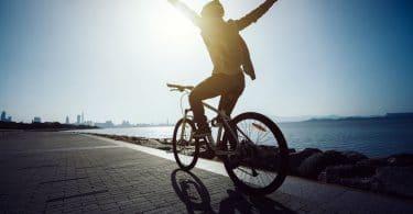 Homem andando de bicicleta com braços para o alto
