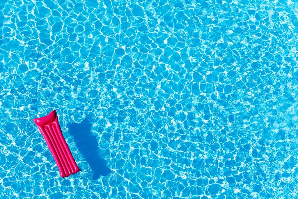Imagem de uma piscina limpa e azul. Ao fundo uma boia inflável na cor pink decora as águas da piscina.