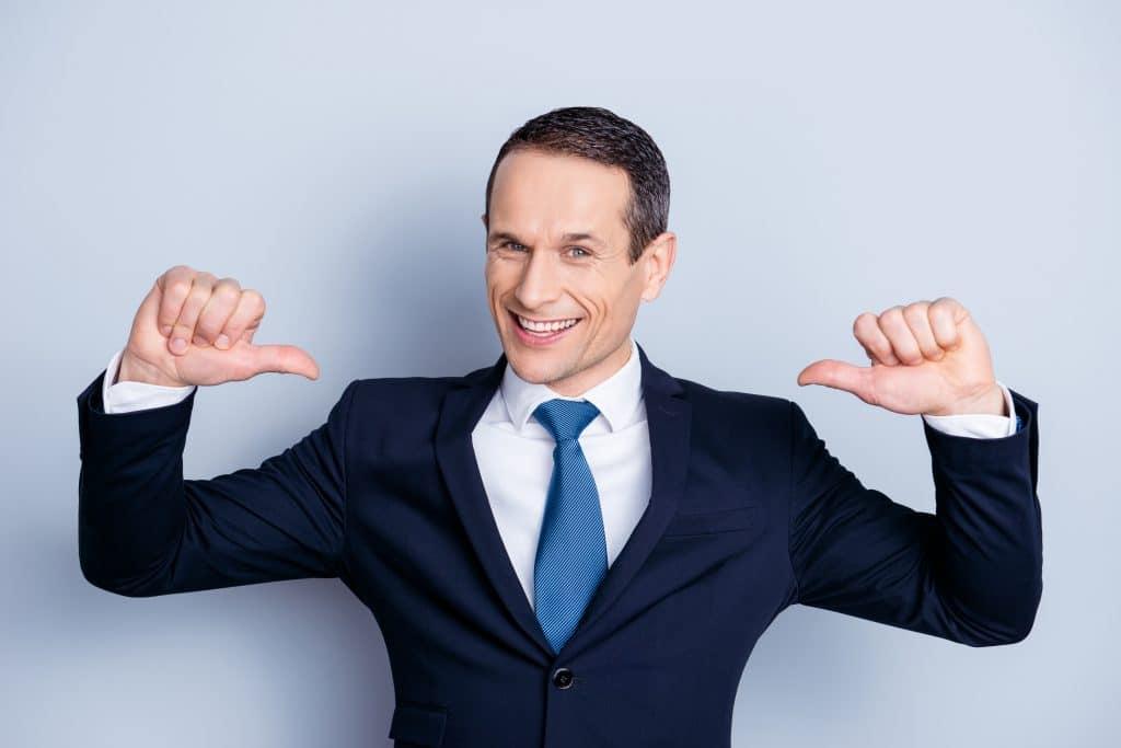 Homem vestindo uma roupa formal - terno cinza, camisa branca e com gravata azul, mostrando com os dois polegares sobre si mesmo.
