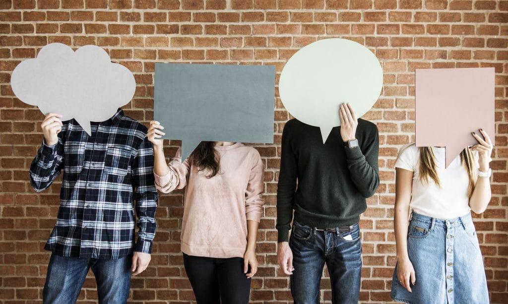 Quatro pessoas, sendo duas mulheres e dois homens, cada um deles segurando cartazes em formato de pensamento. Ao fundo uma parede de tijolinho.