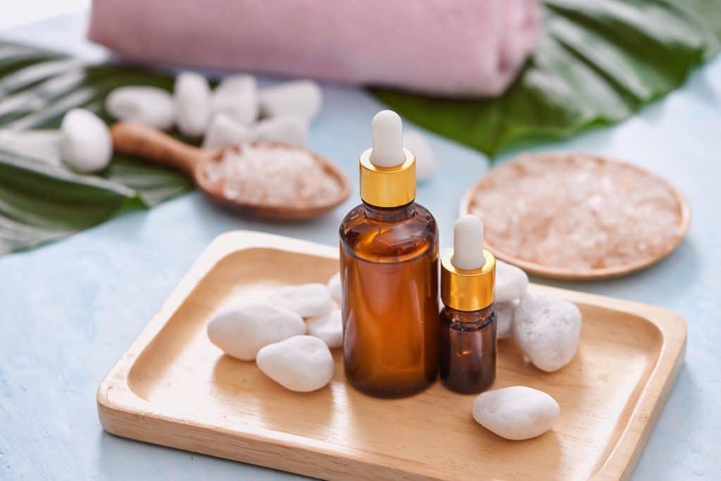 Remédios caseiros para gordura no fígado. Eles já foram produzidos e estão em vidros de conta gotas disponíveis em uma forma de madeira decorada com pedras brancas.