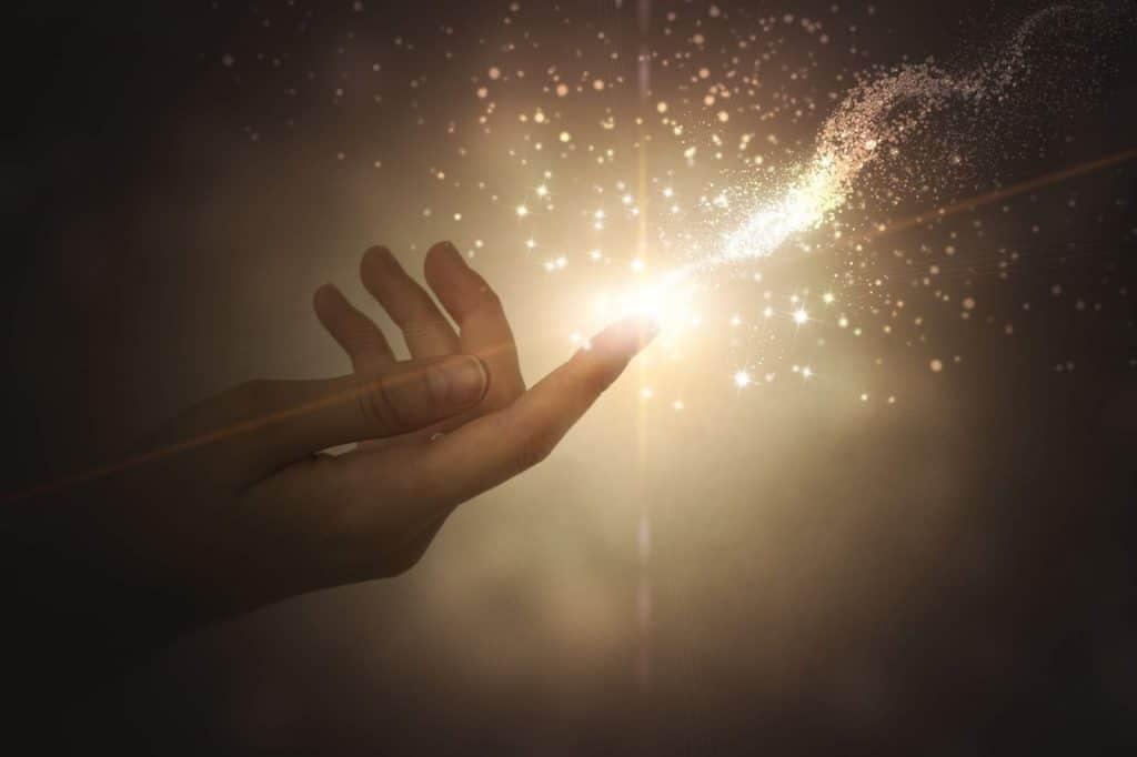 Luz e brilho saindo do dedo de uma mão estendida.