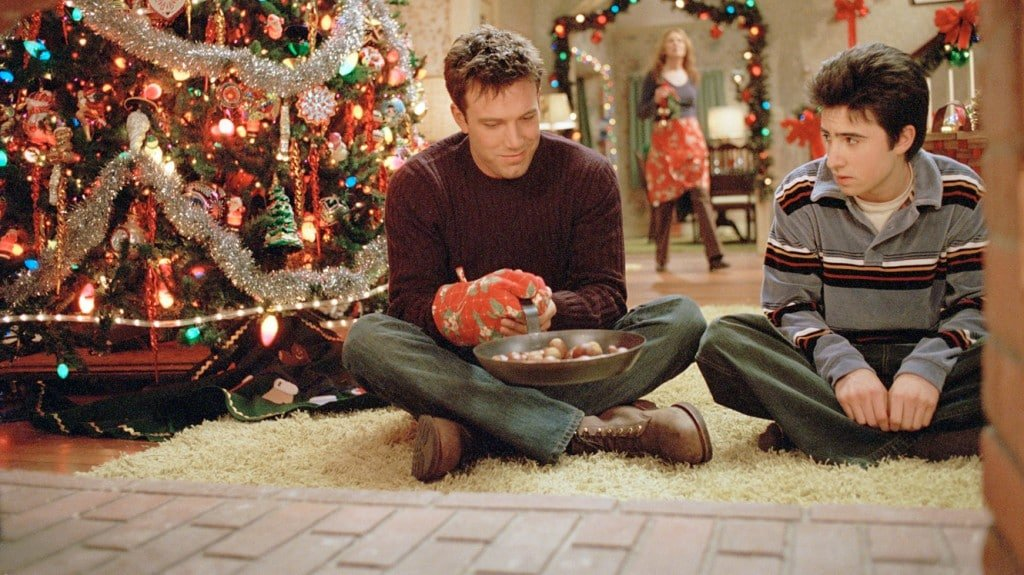 """Cena do filme """"Sobrevivendo ao Natal"""", em que os protagonistas conversam ao lado de uma árvore de Natal."""