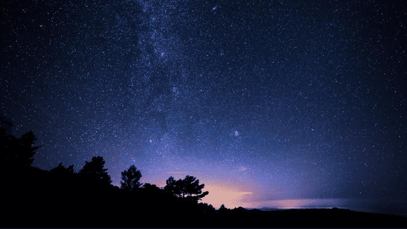 Imagem de um céu de noite, estrelado. Árvores ao fundo.