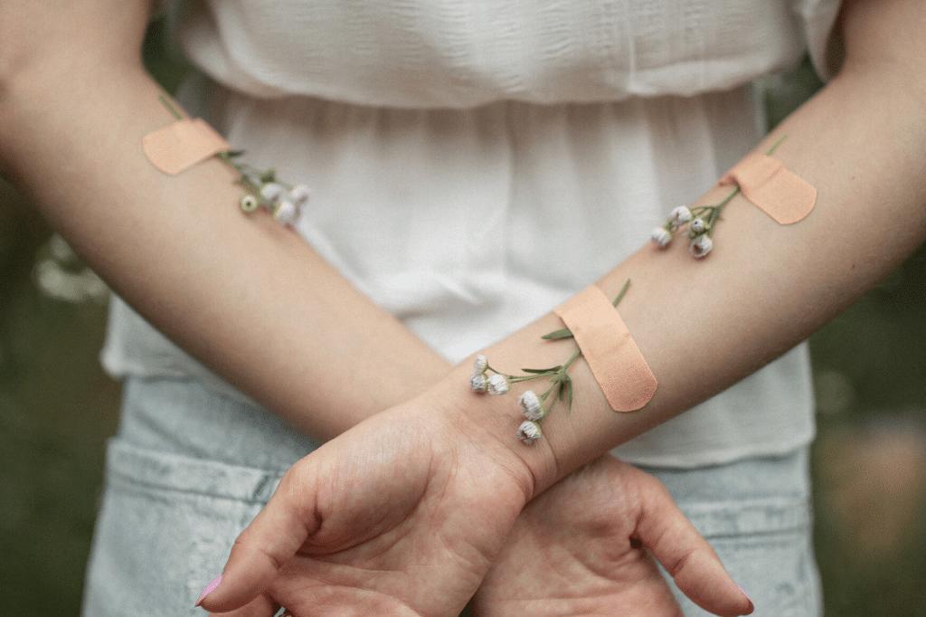 Flores atadas aos braços de uma mulher por curativos.