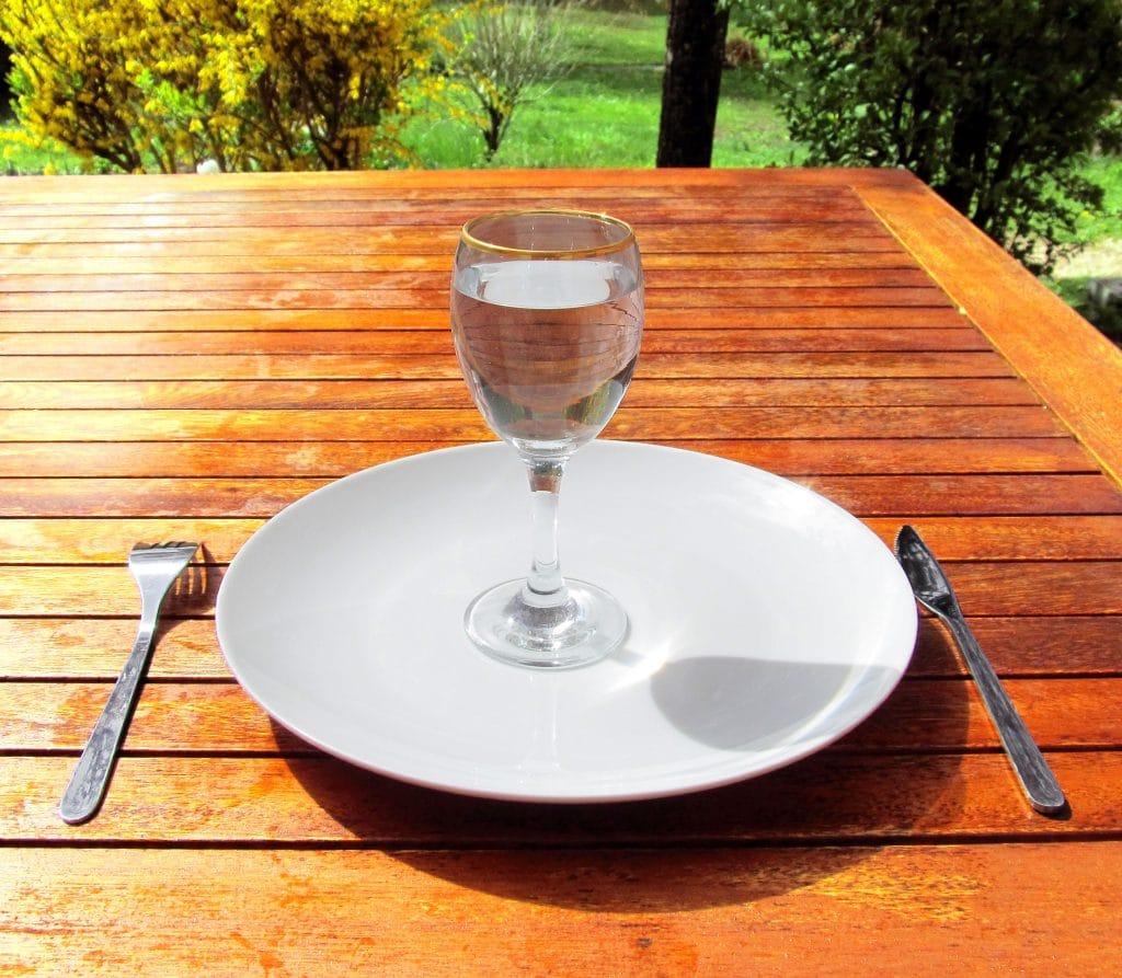 Prato branco vazio em cima de mesa de madeira, com apenas um cálice de água em cima.