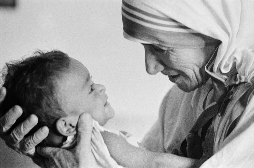Madre Teresa segurando um bebê bem próximo de si, e olhando para seu rosto.