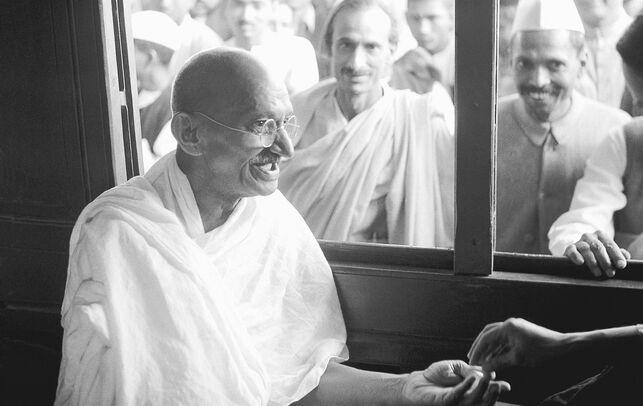 Fotografia em preto e branco de Mahatma Gandhi dentro de um veículo recebendo fãs e seguidores pela janela.
