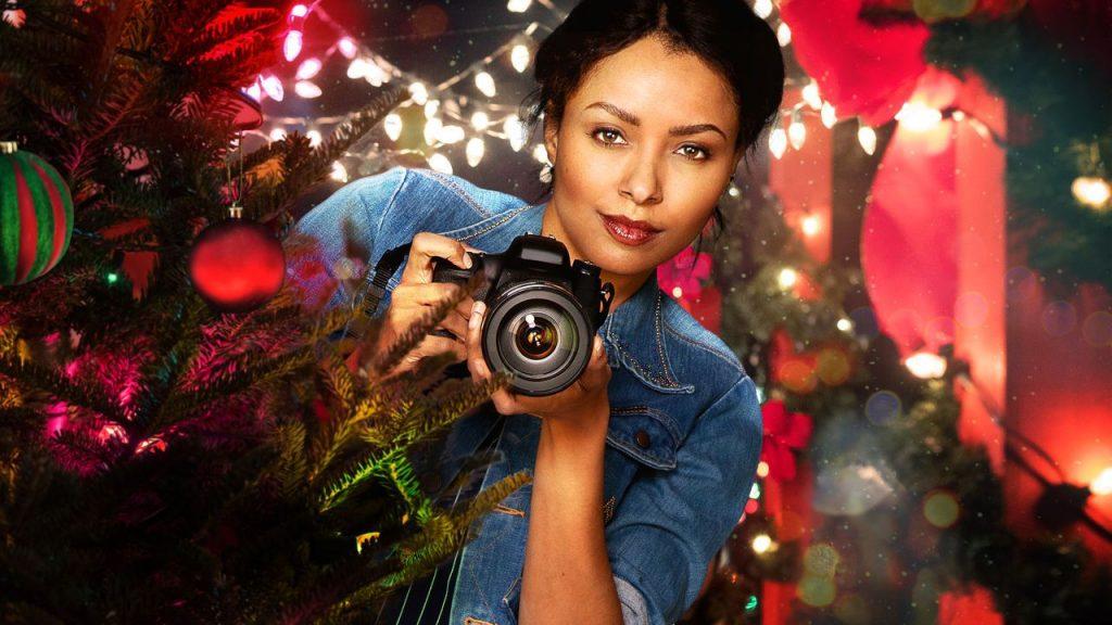 """Pôster do filme """"O Feitiço do Natal"""", em que a protagonista segura uma câmera em meio a decorações de Natal."""