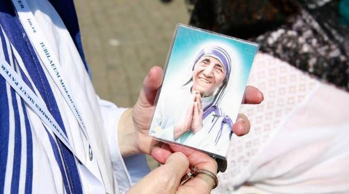 Pessoa carregando figura da Santa Teresa de Calcutá, depois de sua canonização.