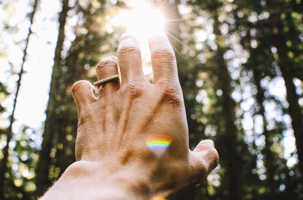 Em uma paisagem natural, uma mão se estende em direção à luz do sol.