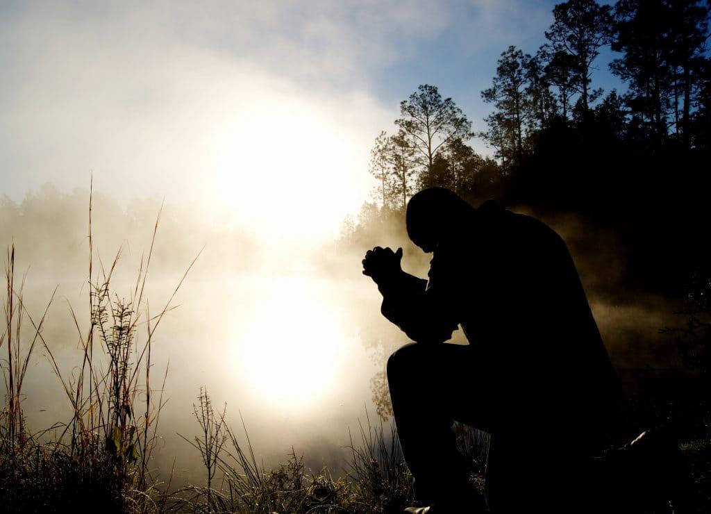 Silhueta de homem de joelhos, com as mãos juntas à altura da cabeça, orando. Ao fundo, há um parque cim um rio ao pôr do sol.