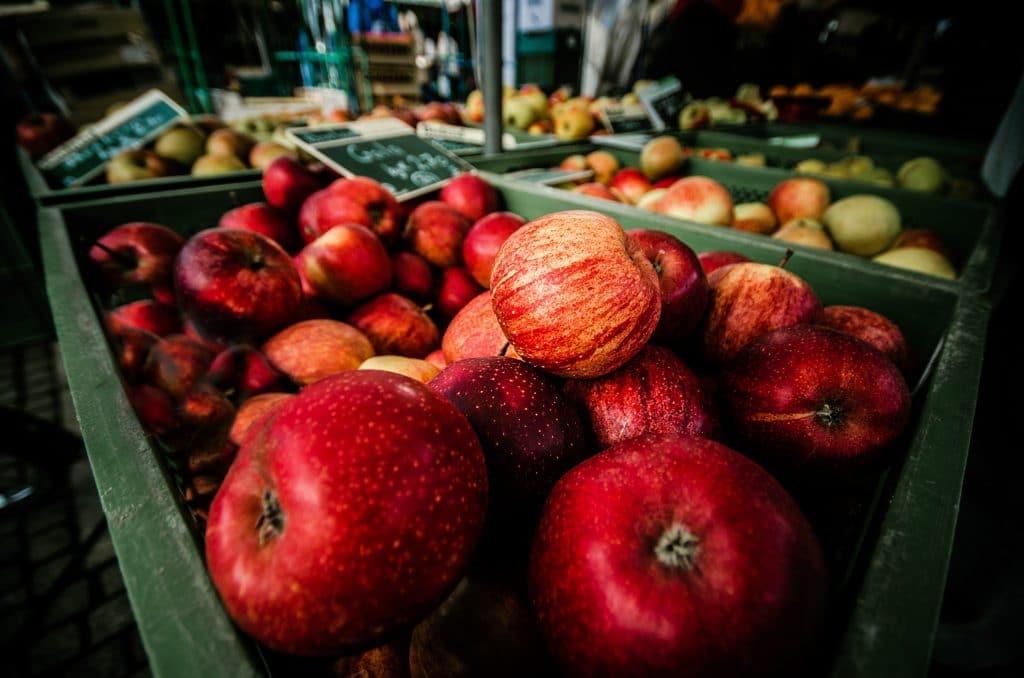 Maças vermelhas em caixa de mercado com frutas ao fundo