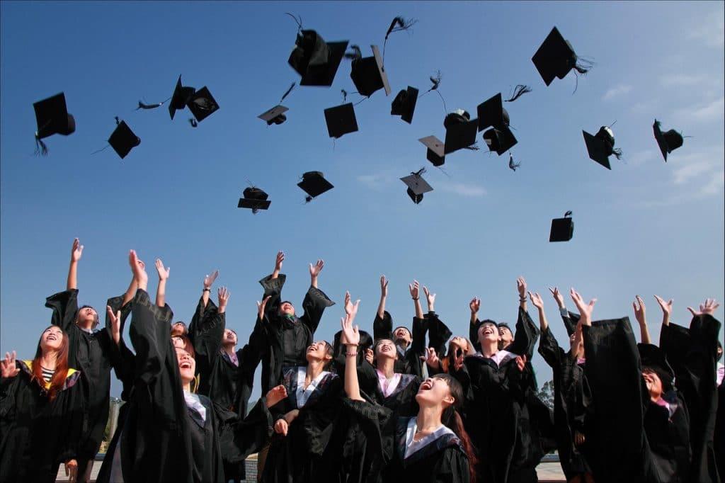 Turma de formandos usando becas enquanto jogam seus chapéus para o alto, em um dia ensolarado.