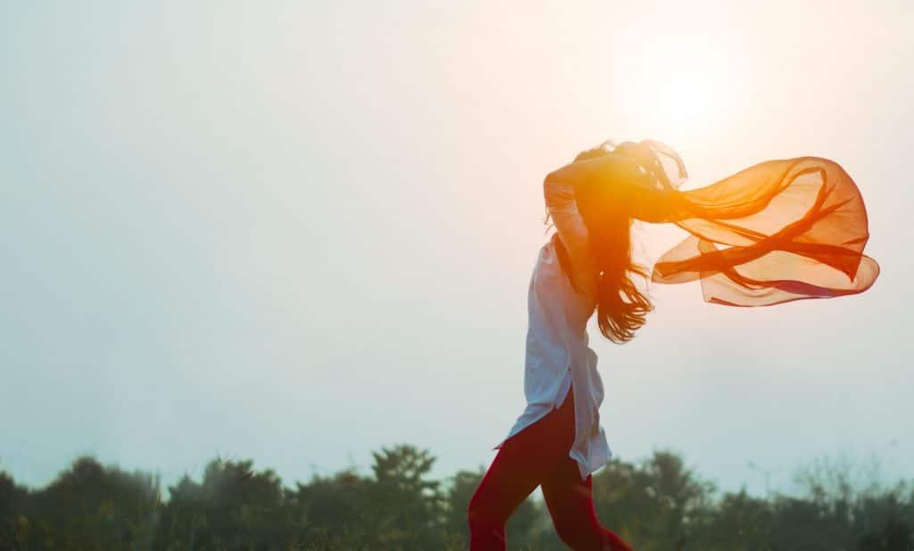 Mulher andando ao ar livre, segurando um lenço esvoaçante atrás da cabeça sob a luz do sol.