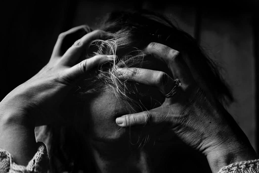Foto em preto e branco de uma pessoa adulta com as mãos percorrendo a cabeça, em sinal de tristeza e desespero.