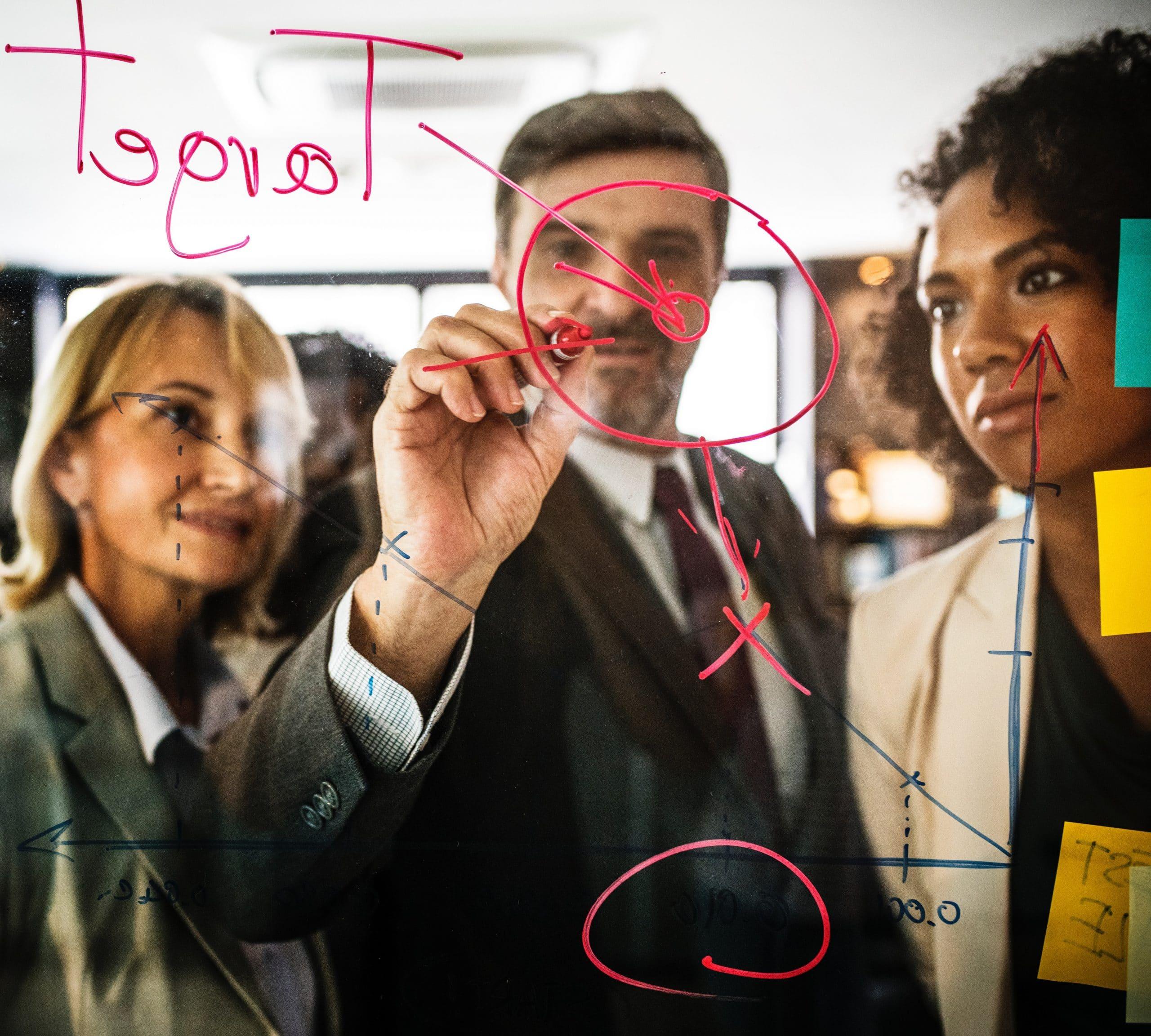 Pessoas escrevendo metas em vidro