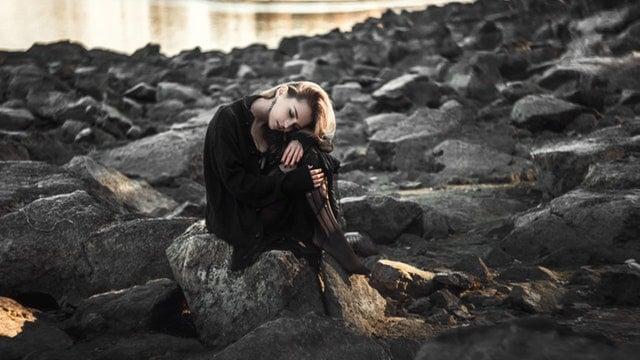 Mulher jovem com roupas pretas e  joelhos flexionados apoia os braços e seu rosto nos joelhos. Ela está sentada em um rochedo preto próximo do mar.