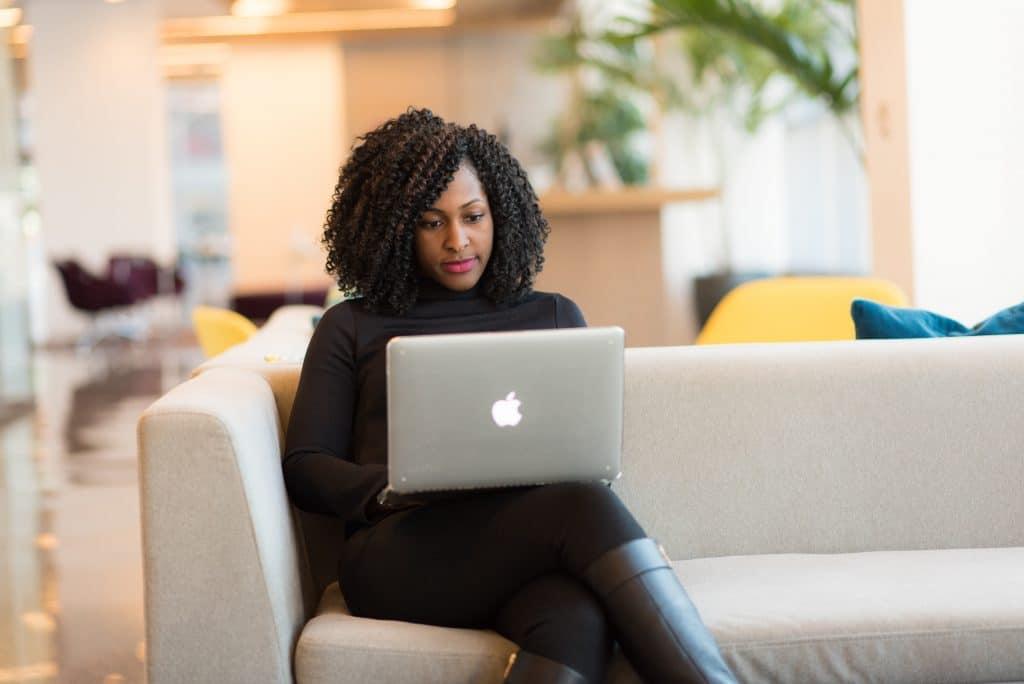 Mulher trabalhando em sofá de escritório com notebook