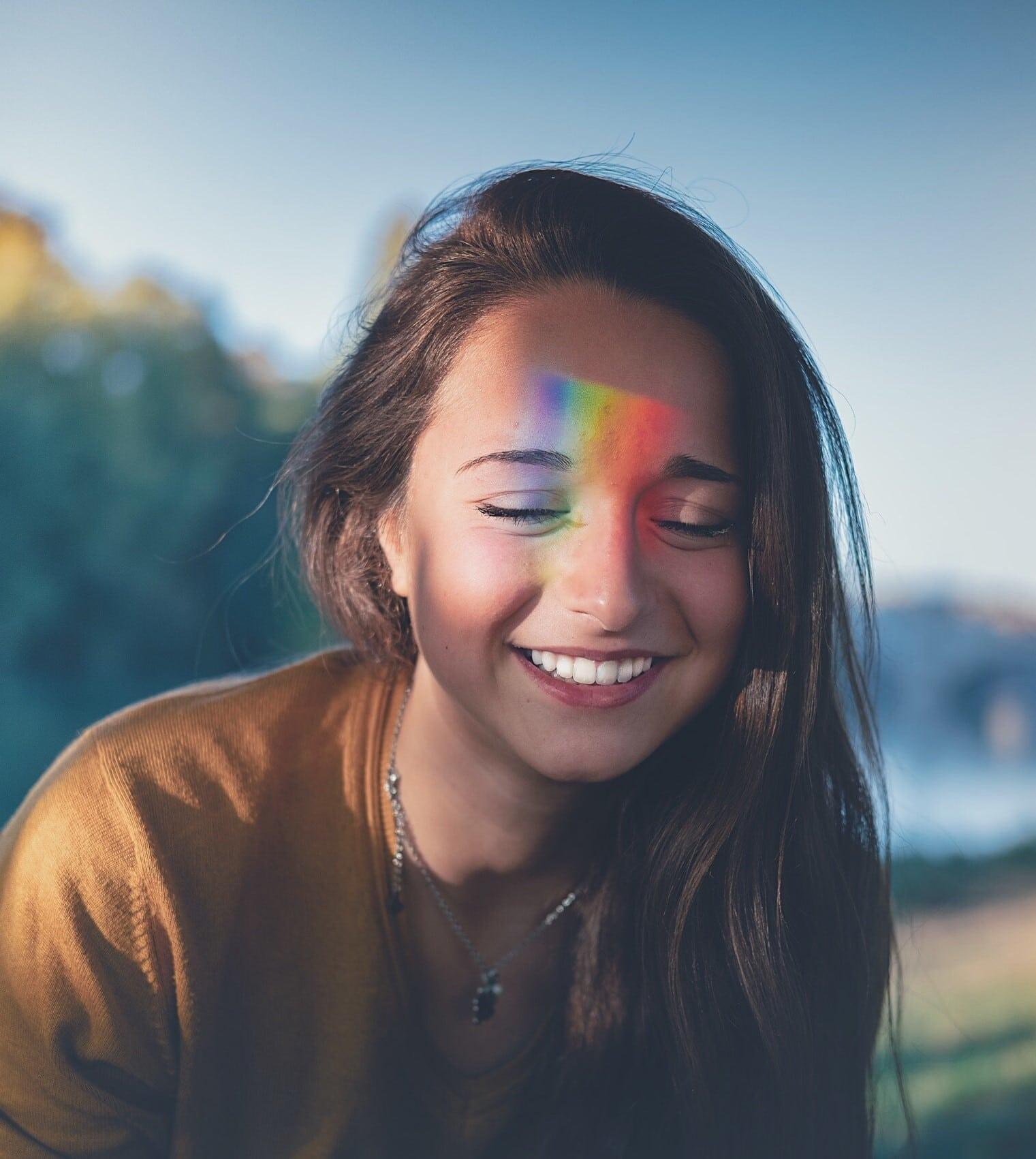 Mulher com os olhos fechado e sorrindo, com arco iris no rosto.