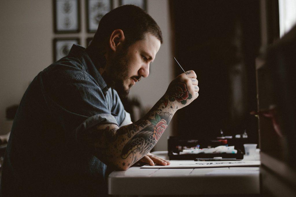 Homem com o braço tatuado, sentado em frente a uma mesinha. Ele está escrevendo algo em um papel.