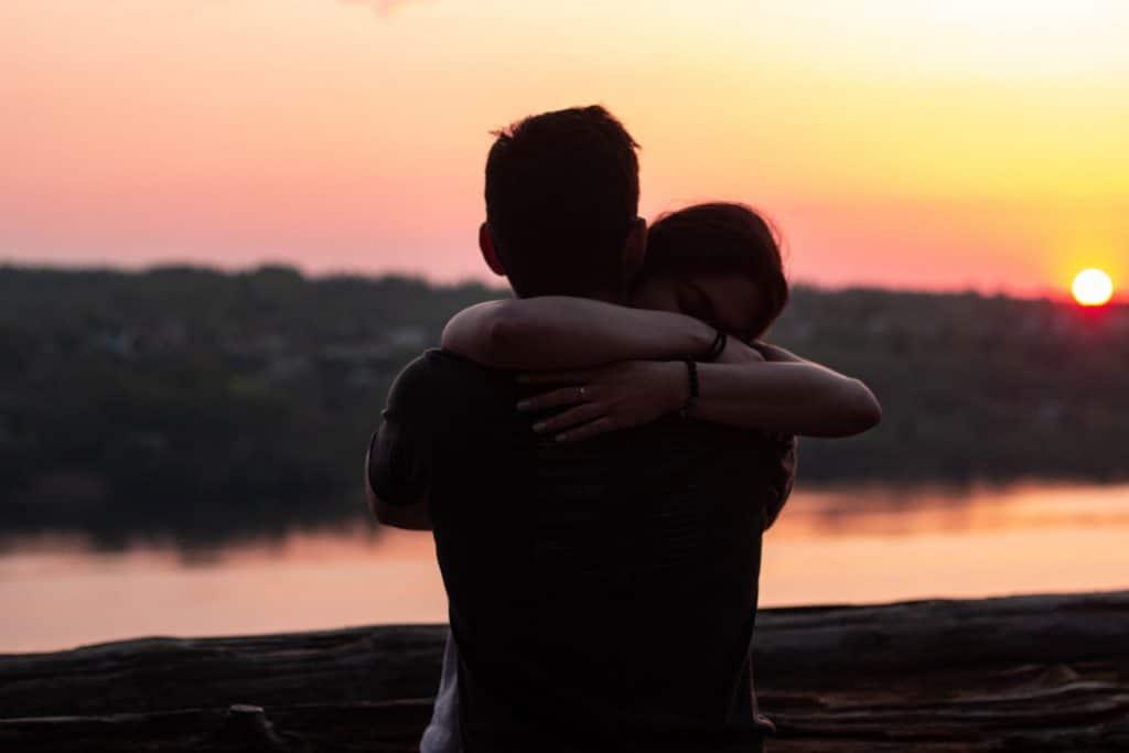 Duas pessoas se abraçando, ao pôr do sol, em frente a um rio.