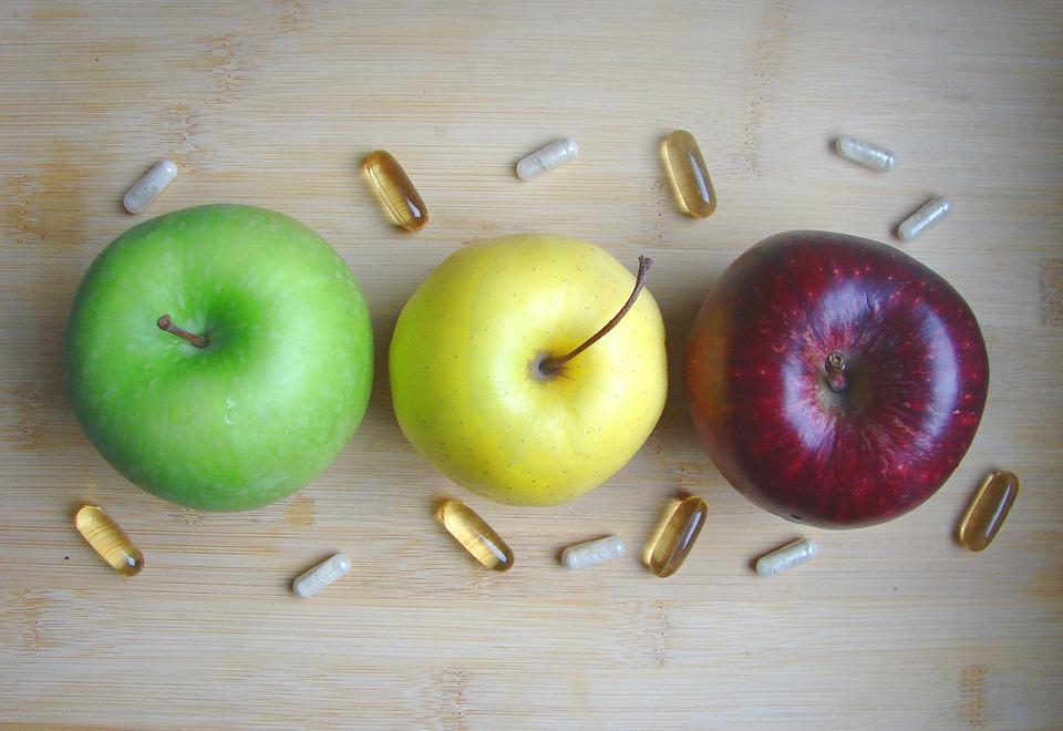 Três maçãs lado a lado, sendo uma verde, uma amarela e uma vermelha, vistas de cima. Ao redor delas estão distribuídas algumas pílulas.