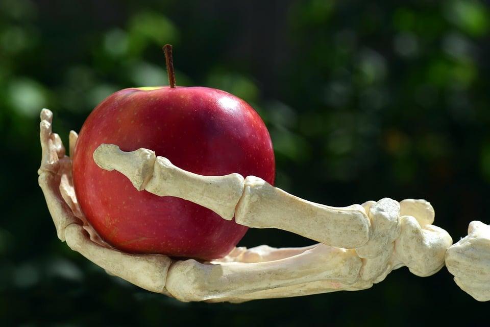 Esqueleto de mão segurando uma maçã vermelha.