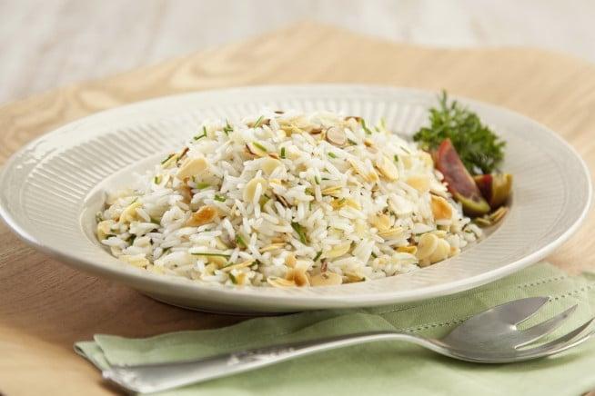 Prato de arroz com amêndoas e garfo ao lado