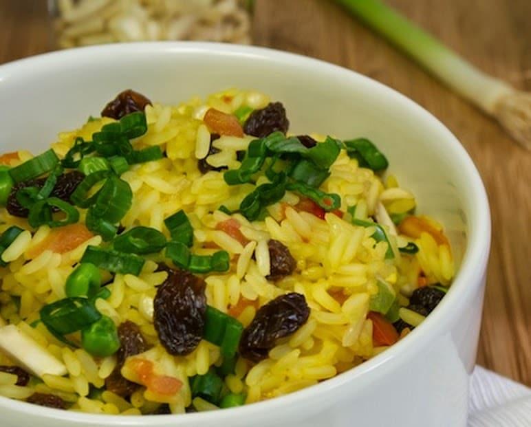 Arroz colorido em uma tigela. É possível ver cebolinha, uva passa e pimentão entre o arroz.