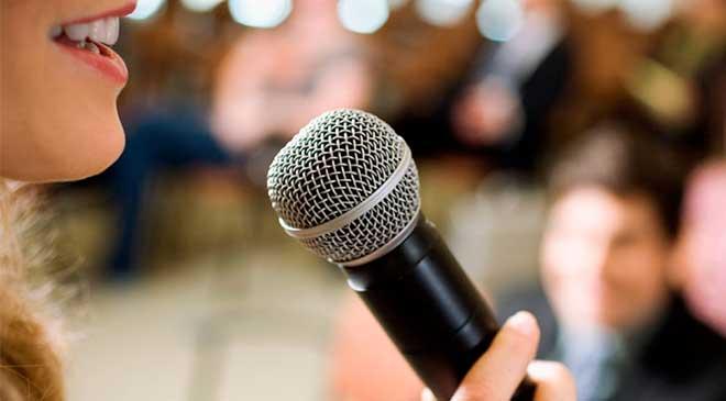 Mulher falando no microfone.