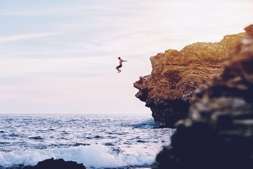 Homem pulando de pedra em mar