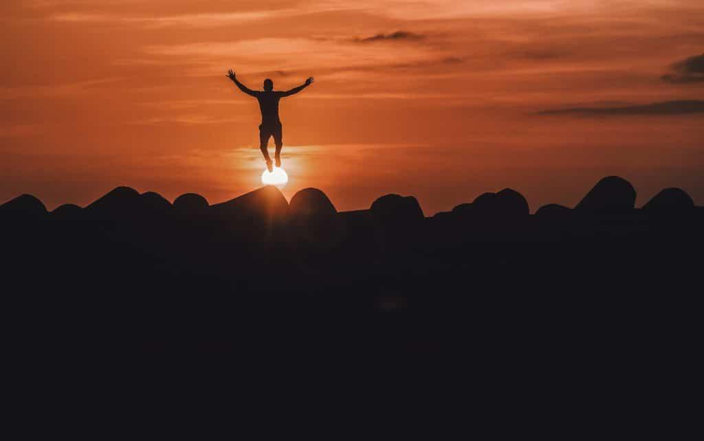 Silhueta de pessoa pulando com sol e montanhas ao fundo