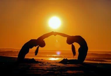 Mulheres na praia em conexão e sol ao fundo