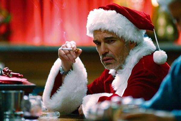 """Cena do filme """"Papai Noel às avessas"""", em que o protagonista, vestido de Papai Noel, fuma um cigarro em um bar."""