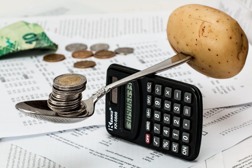 Uma colher em cima de uma calculadora equilibra uma batata de um lado e moedas de outro. Ao fundo, tem-se papeis, boletos e dinheiro em notas e moedas.