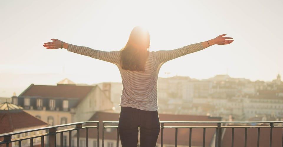 Mulher de braços abertos na varanda sob o nascer do sol.