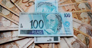 Várias notas de 50 reais em círculo com duas notas de 100 reais ao meio.
