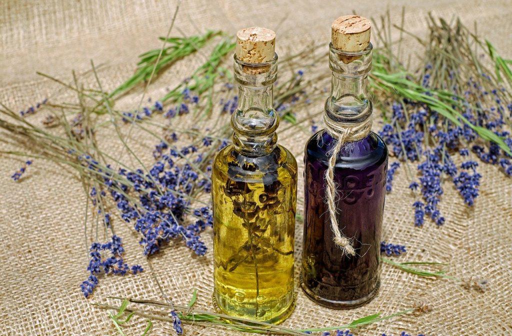 Duas garrafinhas com óleos essenciais, um roxo e um amarelo, fechadas com rolhas, Atrás das garrafas, ramos de uma planta roxa.
