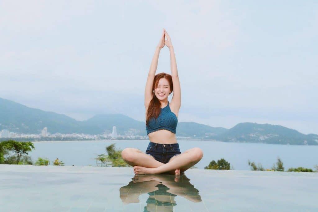 Mulher sorrindo enquanto pratica Yoga ao ar livre, sobre uma paisagem litorânea.