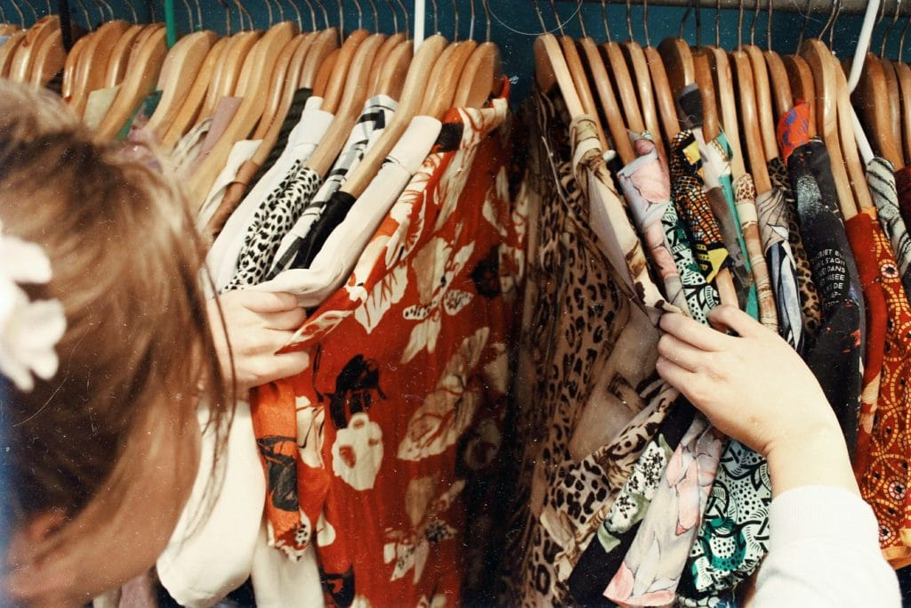 Mulher escolhendo roupa em cabideiro